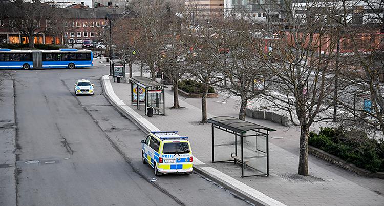 Ett torg för bussar i Sollentuna. Bilden är tagen uppifrån, ner på torget. Nere på torget syns två polisbilar och en blå buss och några träd.