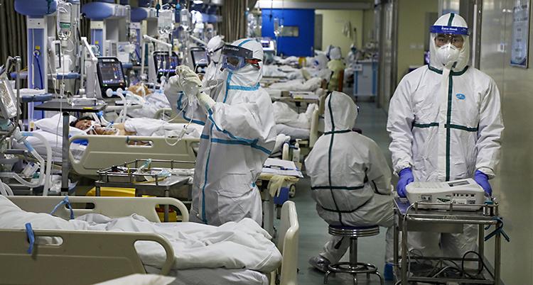 En intensivvårdsavdelning med personal som har overaller, handskar, huvor och masker för ansiktet.