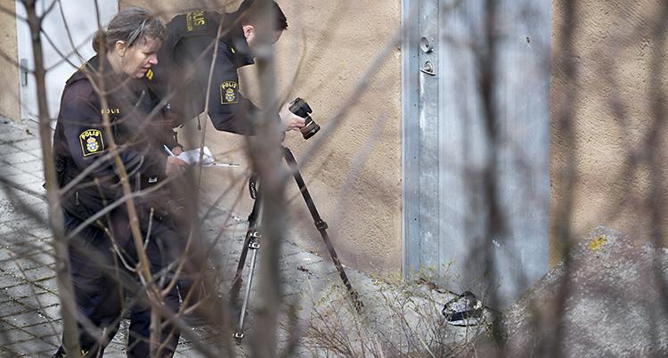 två poliser fotar något på marken utomhus.
