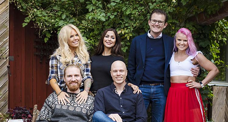 Sex personer står vid varandra och ser glada ut