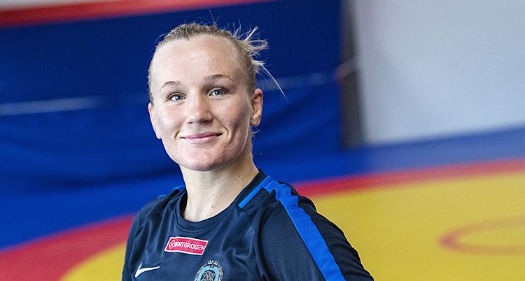 Brottaren Johanna Lindborg står i en sal för brottning. Hon tittar in i kameran. Hon har ljust hår som är uppsatt i nacken.