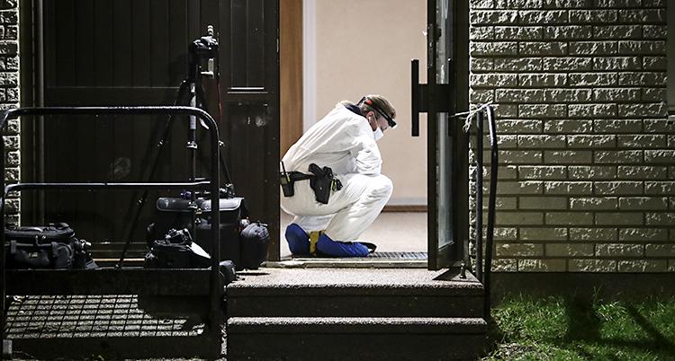 En polis letar bevis. Han står på huk och har skyddskläder på sig.