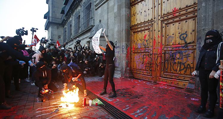 En maskerad kvinna framför presidentens port. Porten är färgad av röd färg som folk slängt på den. Framförkvinnan brinner det på marken. Runt om henne står fler människor.