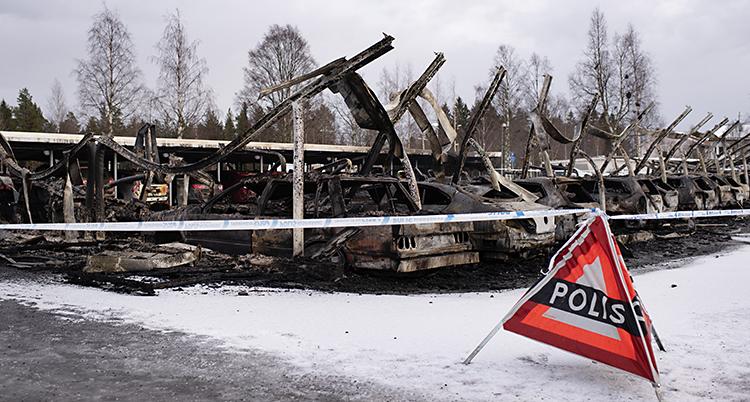 Utbrunna bilar och ett förstört tak över dem. .