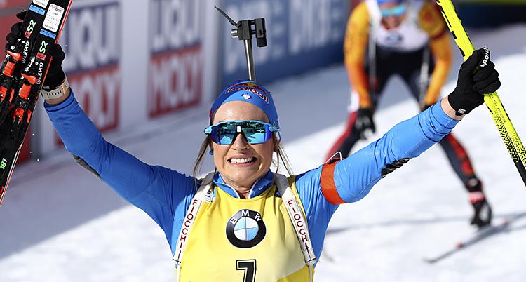 Hon sträcker armarna i luften och ler. I ena handen har hon stavarna och i den andra skidorna.