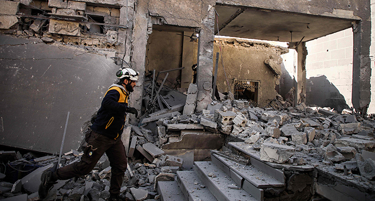 En räddningsarbetare söker efter skadade i ett bombat hus.