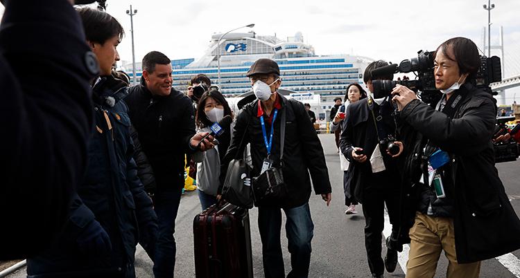 Två personer går med väskor. De har skydd för munnen. Runt dem finns journalister och folk som filmar. I bakgrunden syns en stor båt.