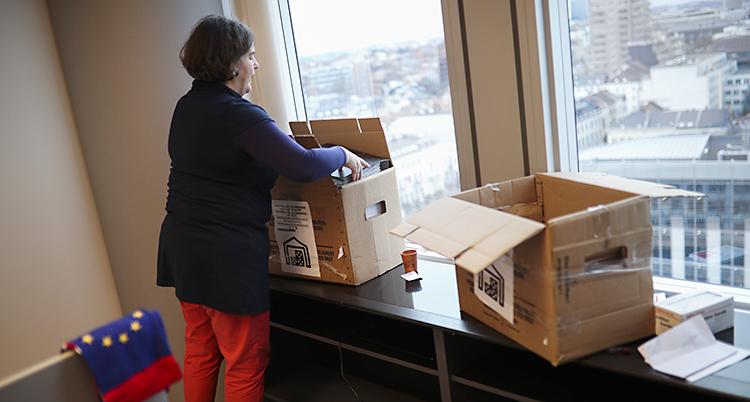 En kvinna med kort brunt hår lyfter en flyttlåda
