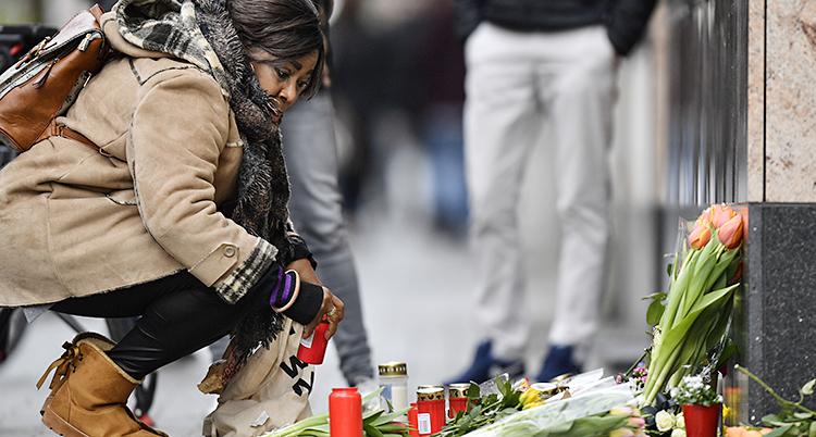 En böjer sig ner mot ljus och blommor på gatan