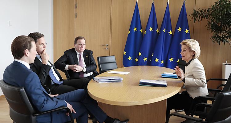 Fyra män och en kvinna sitter vid ett mötesbord med EUs flagga bakom