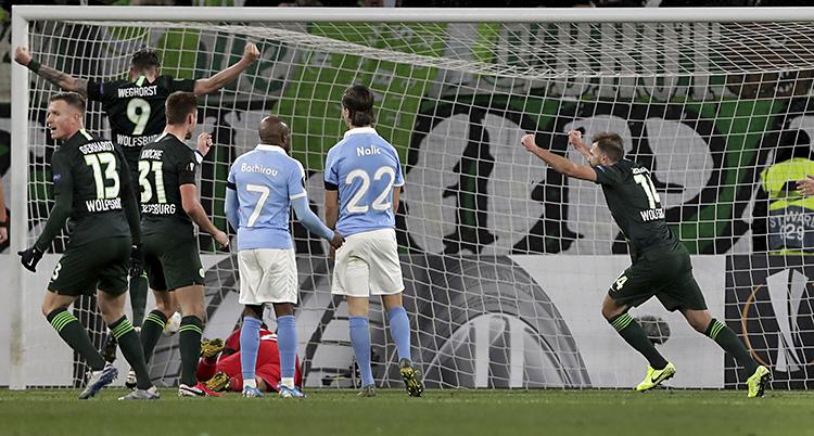 Bilden är från en match i fotboll. Vi ser några spelare i Malmö FF. De har ljusblå tröjor. Spelare i laget Wolfsburg jublar. De har svarta tröjor..