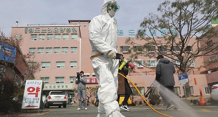 En man i vit skyddräkt går med en slang och sprutar på gatan.