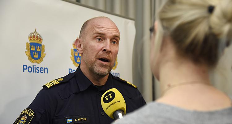 Han har polisuniform och blir intervjuad av en journalist med mikrofon