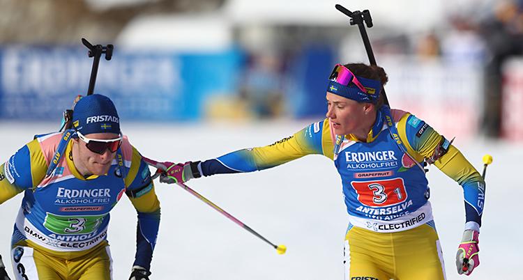 Det är en växling i stafett i skidskytte. Sebastian Samuelsson är till vänster. Hanna Öberg är till högre. Hon lägger sin hand på Sebastians axel. Båda har på sig Sveriges dräkter i gult och blått.