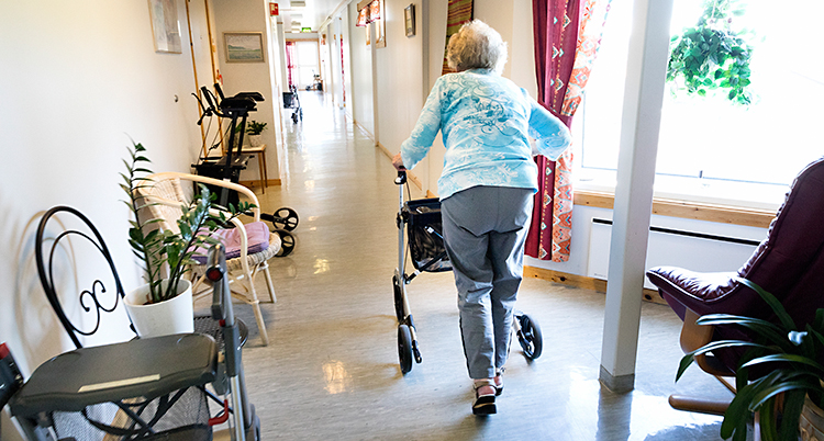 Bilden är tagen på ett boende för äldre människor. En kvinna går i en korridor med rullator. Hon har ryggen mot kameran.