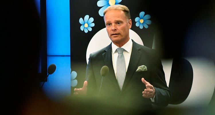 En man står och pratar i mikrofoner. Han pratar till journalister. I bakgrunden syns en skylt med Sverigedemokraternas symbol.