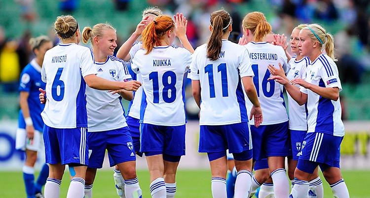 Bilden är från en match i fotboll. Det finska laget samlas när matchen är slut. De har vita tröjor och blå shorts.
