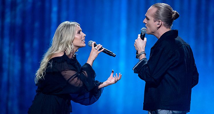 En kvinna och en man står på en scen och sjunger. De tittar på varandra.