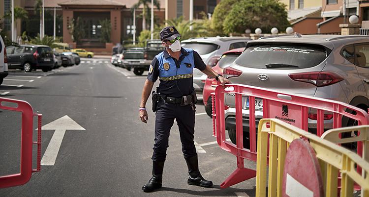 En polis med munskydd står vid en avspärrning på en infart
