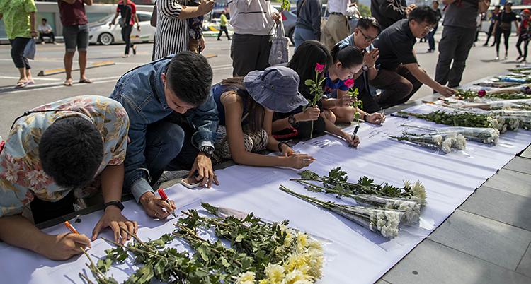 Människor står knä bredvid varandra. De böjer ner sina huvuden. Framför dem ligger blommor. Bilden är tagen utomhus.