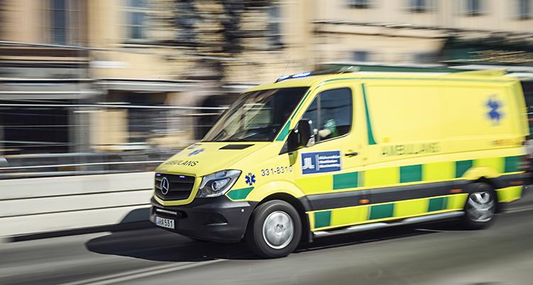 En ambulans som åker på en gata. Bilden är lite suddig för att visa att ambulansen åker fort. Ambulansen är gul med gröna detaljer.
