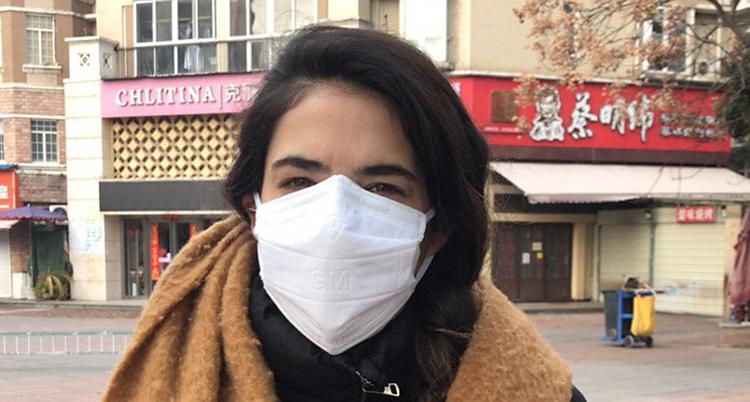 Angelica Kristiansson Herrera har munskydd på sig. Hon står ute i staden Wuhan där hon studerade. Nu har hon fått hjälp att åka hem till Sverige.