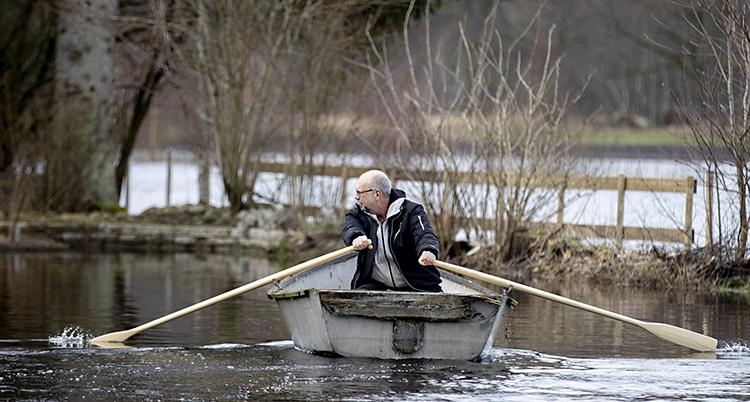 Mikael Jönsson ror en båt för att komma hem till sitt hus.