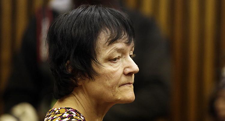 Det är en närbild på en kvinna. Vi ser henne i profil. Hon har mörkt hår. Hon har en lugg och resten av håret slutar under örat. Hon ser allvarlig ut.