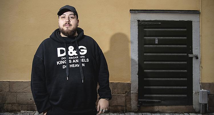 Anis Don Demina har svart keps och en svart tröja med luva på sig. Han har en gul husvägg bakom sig.