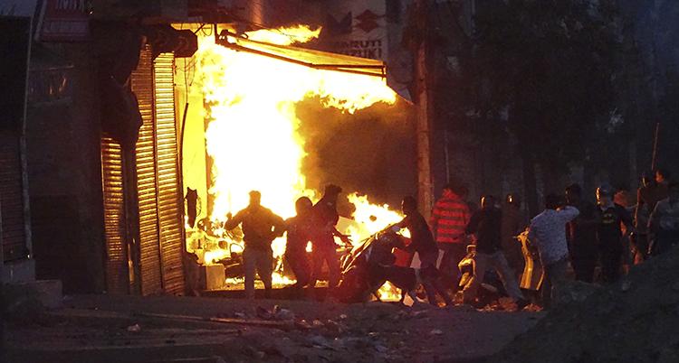 En affär brinner på en gata i New Delhi. Det är kväll. Några människors skuggor syns.