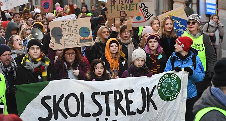 Greta Thunberg och flera andra elever går tillsammans. De har skyltar i händerna.
