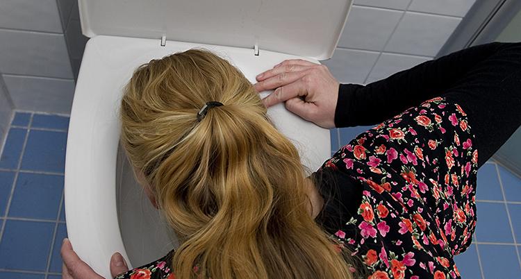 En illamående kvinna hänger över en toalettstol.