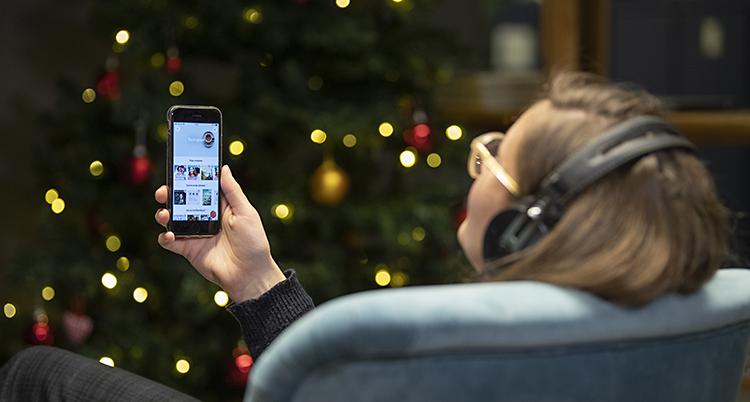 En kvinna lyssnar på en ljudbok i mobilen.