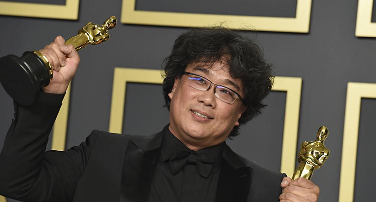 Bong Joon Ho håller upp en statyett med Oscars i varje hand. Han har glasögon och svart hår.