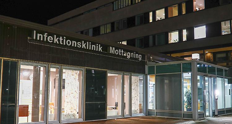 En bild på sjukhuset i Göteborg. Det står infektionsklinik på en stor skylt. Det är kväll på bilden. Det lyser i flera fönster.