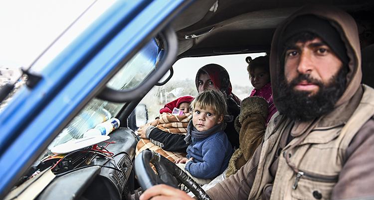 Vuxna och barn trängs i förarhytten på en lastbil.