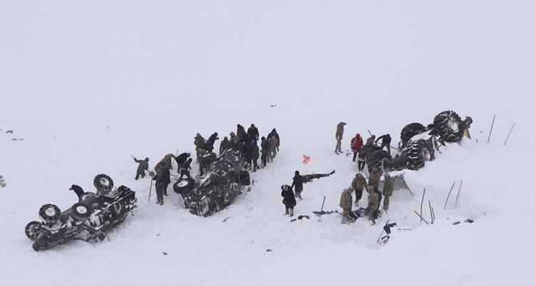 Bilar och människor syns i snön. Bilarna ligger upp och ner. Människor gräver i snön.