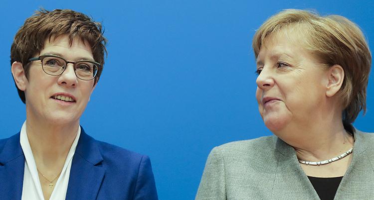 De två tyska politikerna Annegret Kramp-Karrenbauer och Angela Merkel står bredvid varandra. Annegret står till vänster. Hon har glasögon och en blå kavaj. Hon tittar rakt fram. Angela Merkel står till höger. Hon har en grön kavaj. Hon tittar på Annegret.