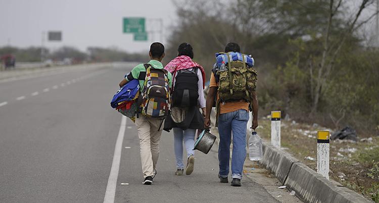 Tre personer går längs en motorväg med stora ryggsäckar på ryggen