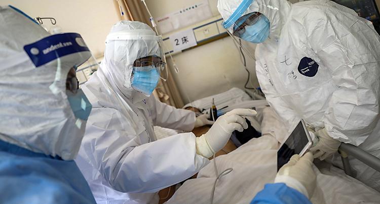 En smittad patient i Kina blir undersökt på ett sjukhus i Wuhan. Personalen har vita skyddskläder och masker för ansiktet.
