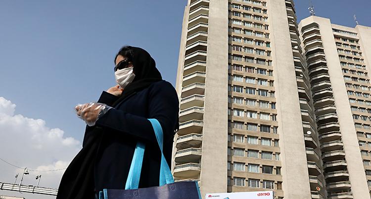 En kvinna i Iran har mask i ansiktet. Bakom henne finns ett högt hus.