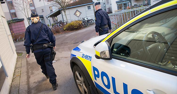 Två poliser går framför en parkerad polisbil. De är på väg mot ett bostadsområde.