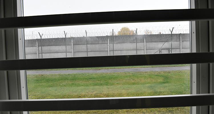 Bilden är tagen från en cell på ett fängelse. Ut genom fönstret. Det finns ribbor för fönstret. Längre bort syns en mur med taggtråd.