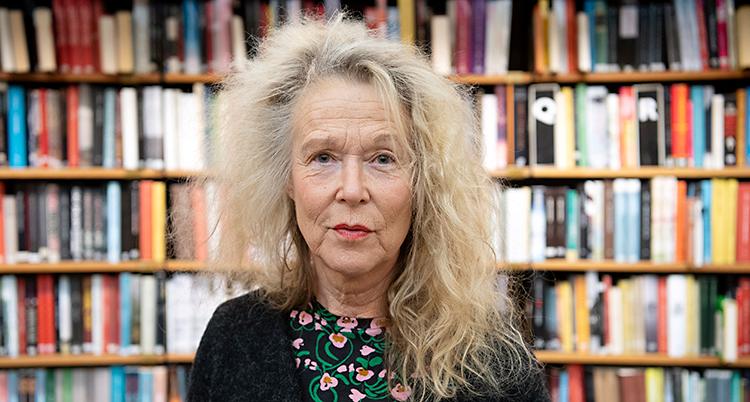 En kvinna med ljust hår. Håret är långt och stort. Hon är i ett bibliotek. Bakom syns hyllor med böcker.
