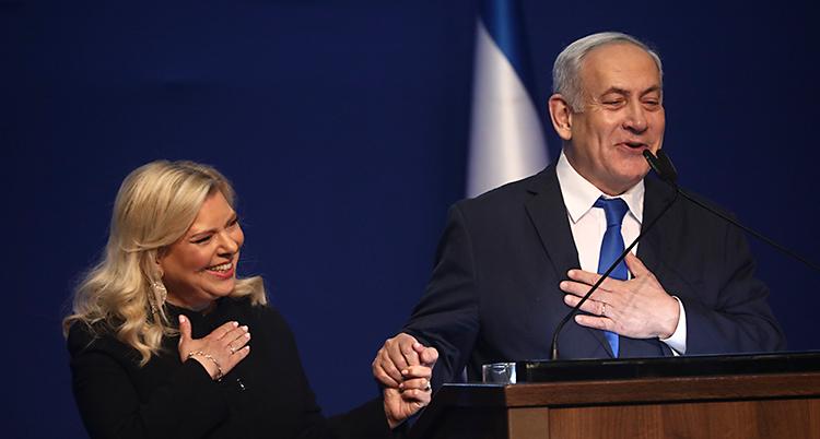 Han står i en talarstol och skrattar. En kvinna står bredvid och klappar i händerna.