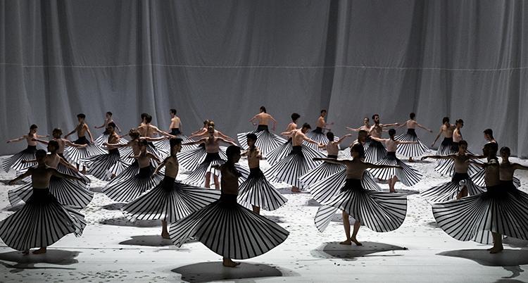 En scen på en opera. Golvet är rutigt i svart och vitt. En massa dansare som dansar balett.