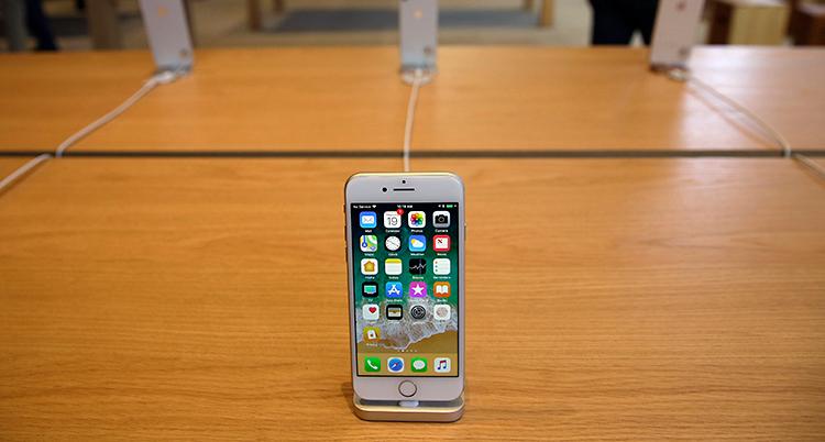 En mobiltelefon från företaget Apple står på ett bord av trä.