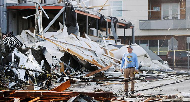 En man med keps står och tittar på flera hus som har blivit förstörda av en storm.