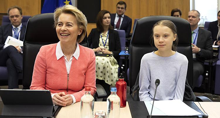 De sitter bredvid varandra vid ett skrivbord. EUs ledare ler stort. Greta ser mer allvarlig ut.