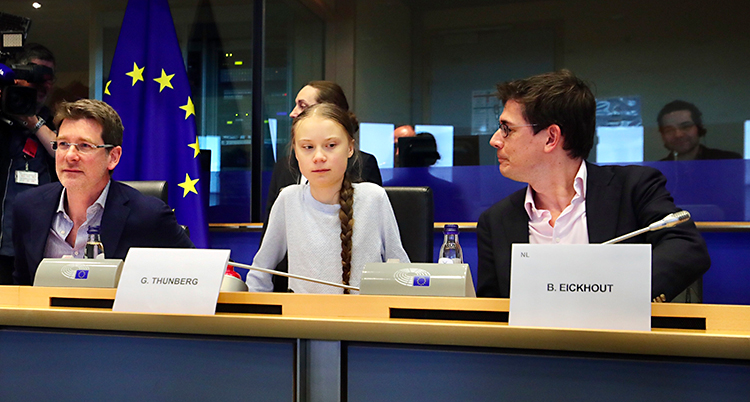 Greta Thunberg sitter vid ett bord med två politker bredvid sig.